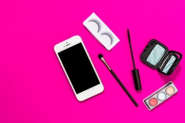Mobile phone; makeup brush; eyelashes; mascara brush and eyeshadow palette on pink backdrop Free Photo