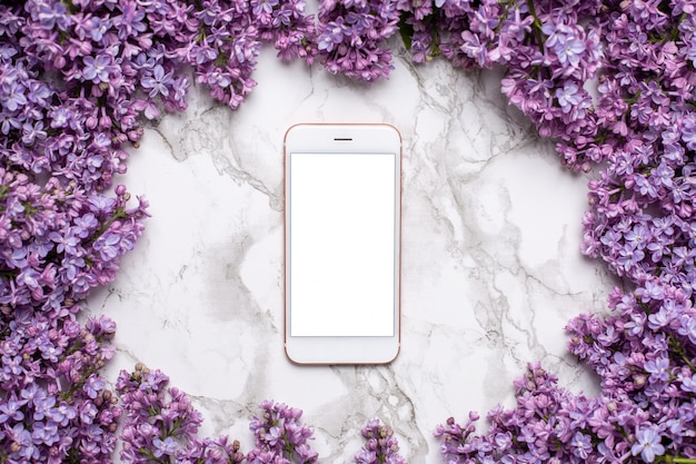 Mobile phone on marble table and lilac flowers Premium Photo