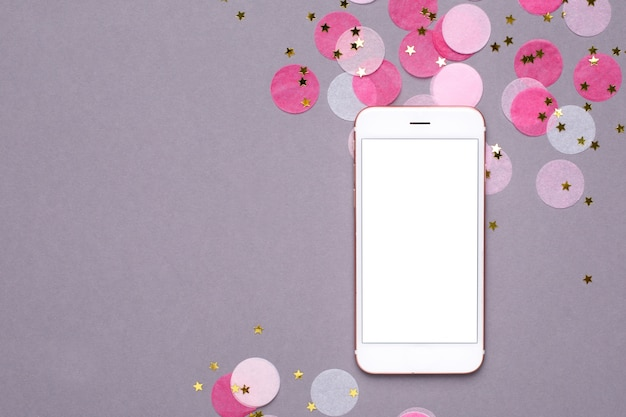 Mobile phone mock up and pink confetti with gold stars on gray Premium Photo