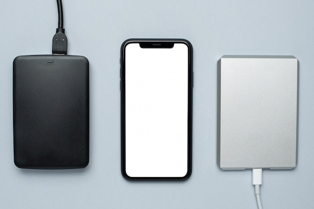 Mobile phone mock up and removable hard drives on gray Premium Photo