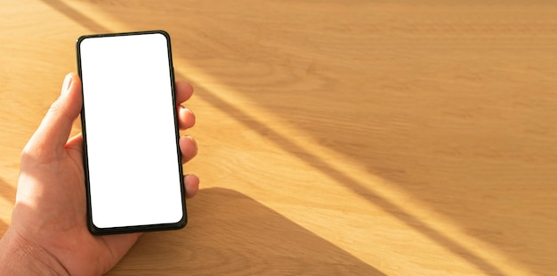 Mobile phone mockup with white screen for your app advertise in male hand over wooden background, c