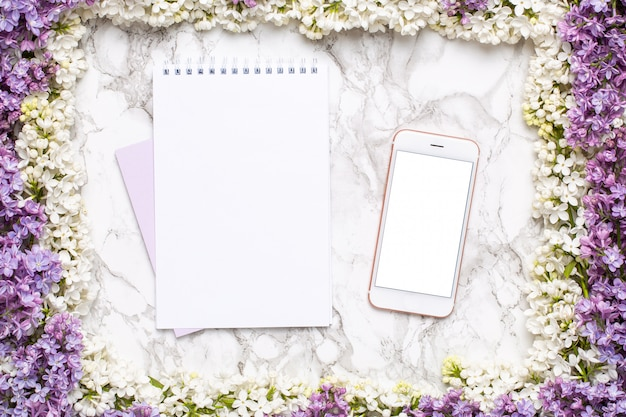 Mobile phone, notebook and frame of white and lilac flowers on marble table in flat lay style. Premium Photo