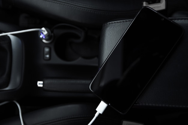 Mobile phone, smartphone charge battery, charging in the car plug close up Premium Photo