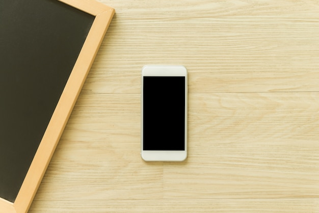 Mobile phone with blank screen and blank wooden blackboard frame on ...