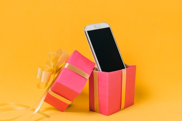 Mobile phone with blank screen in pink gift box Free Photo