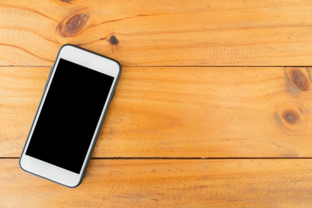 Mobile phone with blank screen on wooden table background. top view with copy space. Free Photo