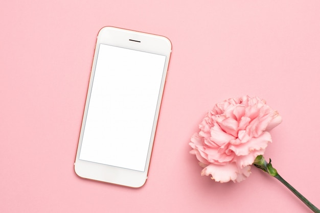 Mobile phone with pink carnation flower on a marble background Premium Photo
