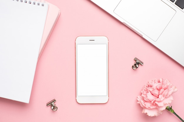 Mobile phone with pink carnation flower and notebook on a marble background Premium Photo