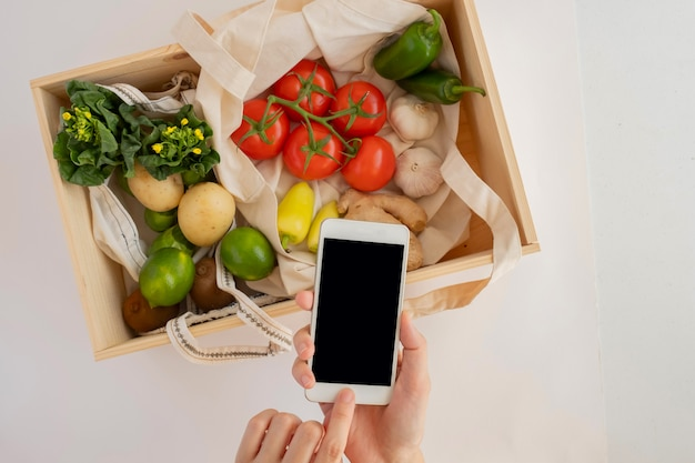 Мобильный телефон с эко сумкой и свежими овощами в деревянной коробке. онлайн продуктовый и органический фермер продукт покупки приложений. еда и кулинарный рецепт или подсчет питания. Premium Фотографии