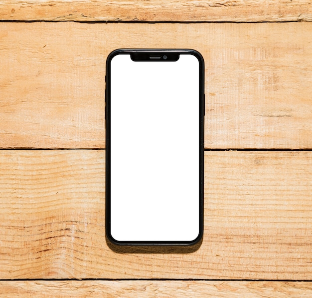 Mobile phone with white screen display on wooden desk Free Photo