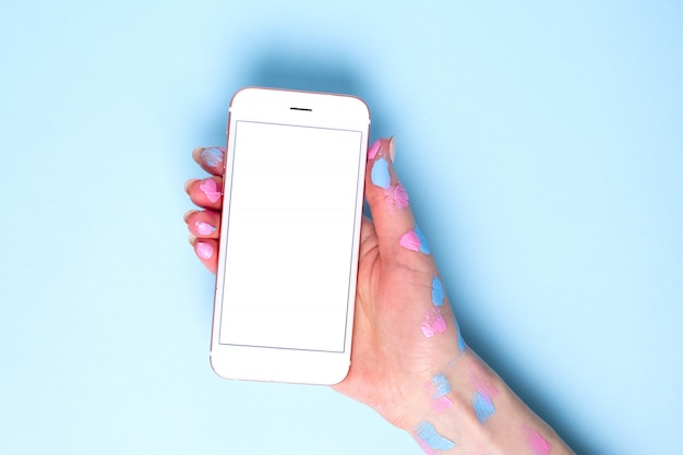 Mobile phone in women's hands with watercolor on blue surface Premium Photo