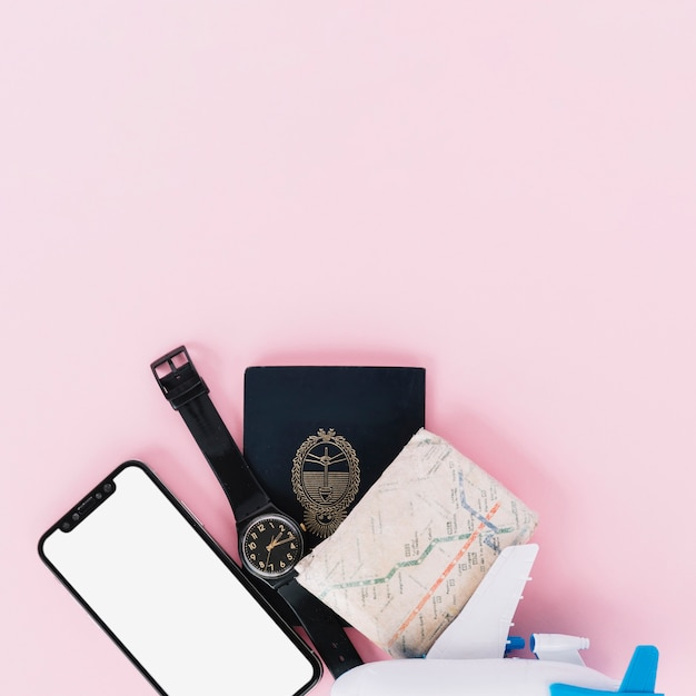 Mobile phone; wristwatch; passport; map and miniature airplane on pink background Free Photo