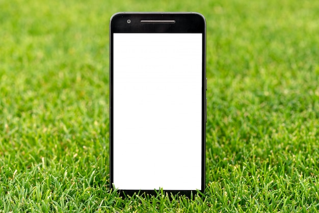Mobile smart phone mockup with white screen on green grass background. Premium Photo