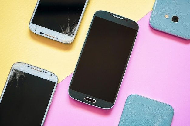 Mobile smartphones with broken glass screen on pink and yellow. Premium Photo