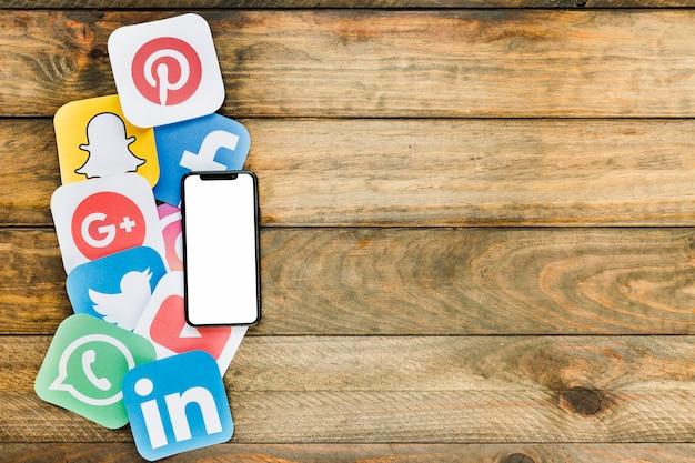 空白の画面を持つ携帯電話は、ソーシャルネットワーキングのアイコンを木製のテーブル上に配置 Premium写真