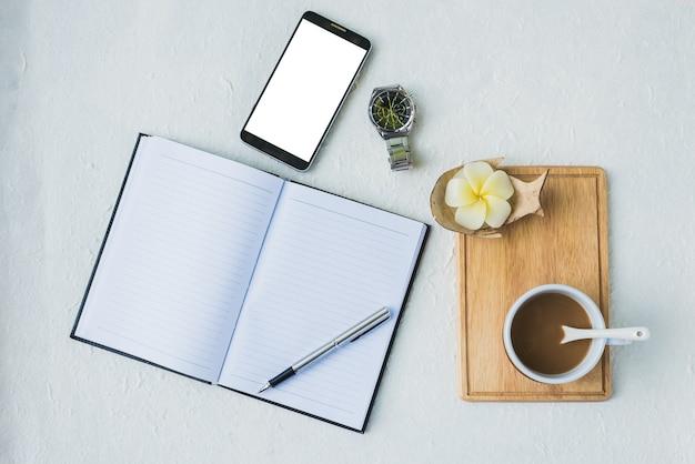 カレンダーの本、コーヒー、時計、薬とmoblieの概念を持つオフィスの職場 Premium写真