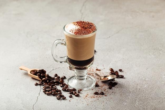 콩으로 장식 된 회색 콘크리트 배경에 유리 머그잔에 모카 치노 커피 프리미엄 사진