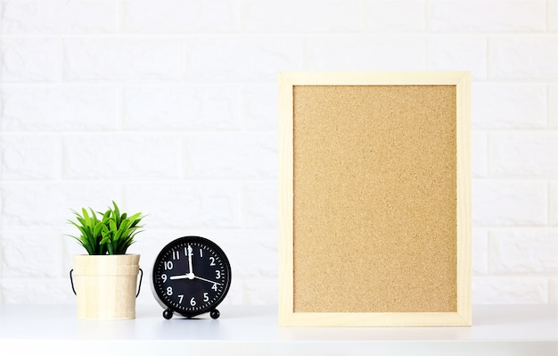 Mock up blank cork board with watch,green plants on white brick wall,minimal style Premium Photo