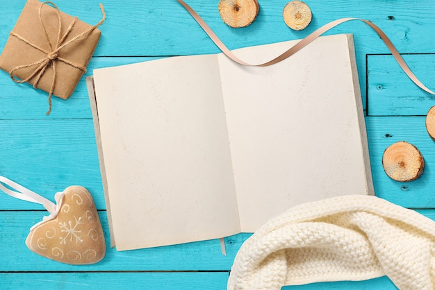Mock up blank open notepad, christmas gifts on a turquoise wooden Premium Photo