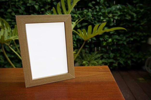 레스토랑 카페 바에서 나무 테이블에 빈 흰색 프레임 서 모의. 텍스트를위한 공간입니다. 제품 디스플레이 몽타주. 프리미엄 사진