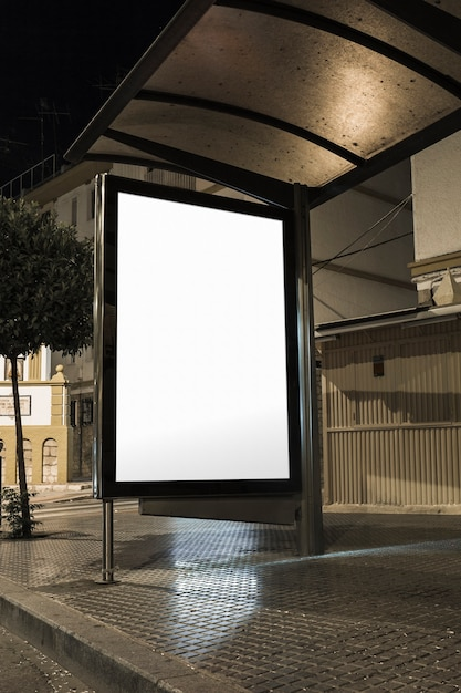 Mock up of blank white vertical light box on a bus stop in a city at night Free Photo