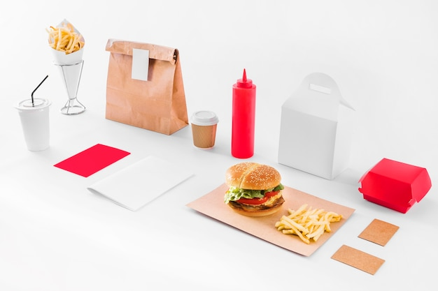 Mock up of burger; french fries; parcel; sauce bottle and disposal cup on white backdrop Free Photo