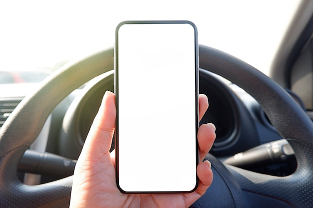 Mock up driver hand holding phone in car empty clear screen for text Premium Photo