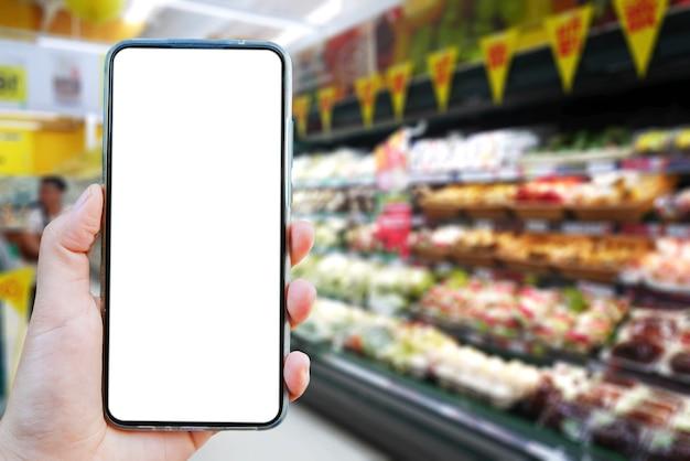Копируйте изображение руки, держащей пустой экран смартфона на размытом фоне. Premium Фотографии