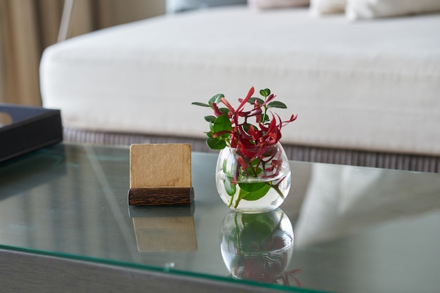 Mock up label stand with flower water vase on table  in room for welcome reception concept Premium Photo