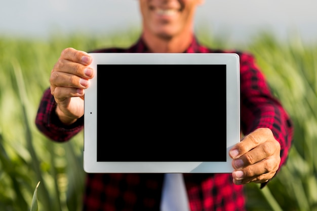 Mock-up man holding a tablet in a field Free Photo