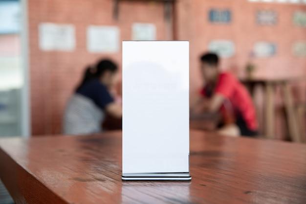 Bar restaurant-cafeteriaのテーブルの上にメニューフレームをモックアップします。 無料写真