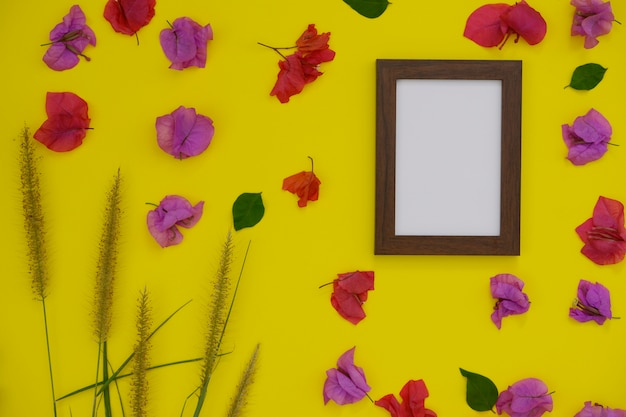 Mock-up photo frame with space for text or picture on yellow background and tropical flowers. Premium Photo