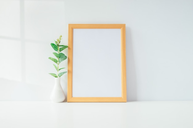 Mock up portrait photo frame with green plant on table, home decoration. Premium Photo