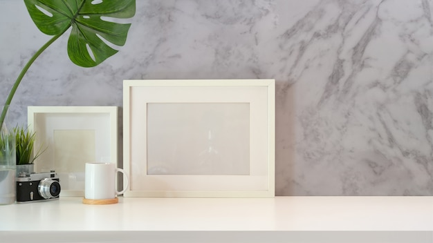 Mock up poster empty frame on minimal workspace Premium Photo