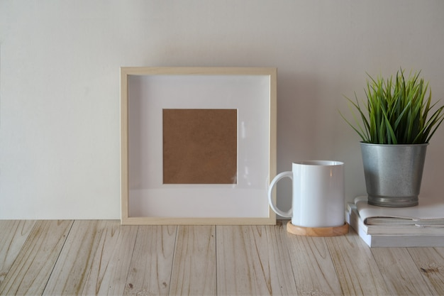 Mock up poster or photo frame on wood table Premium Photo