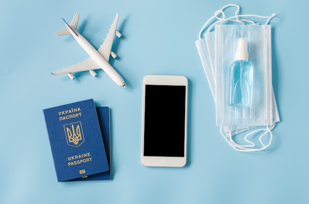 Mock up of smartphone with airplane model, passports of ukraine, face mask and hand sanitizer spray Premium Photo