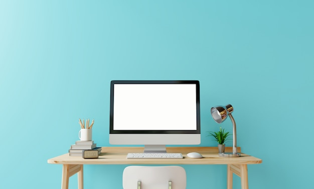 Mock up work space computer with blank screen on wood table in blue pastel room. Premium Photo