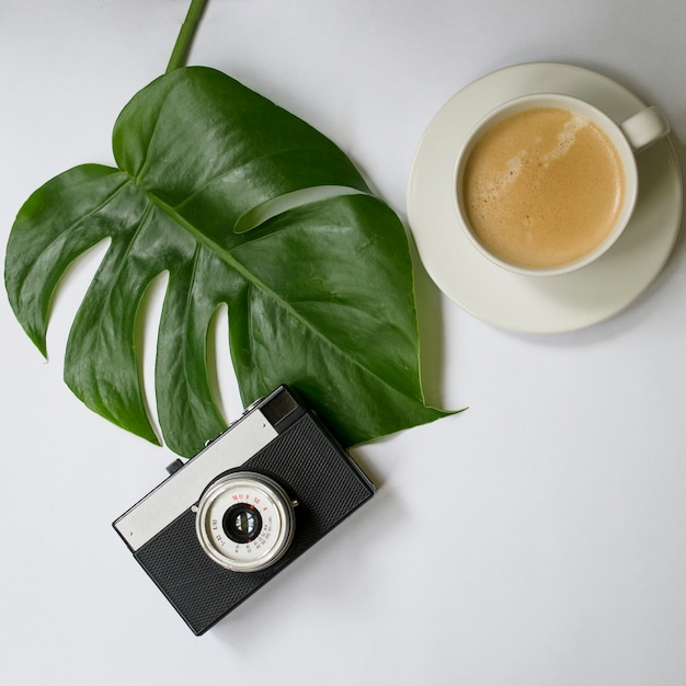 Mock up workspace with tropical palm leaf, notebook, camera, pen, card and coffee cup Premium Photo