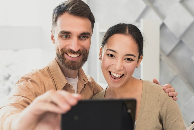 Mock-up young friends taking selfies at office Free Photo