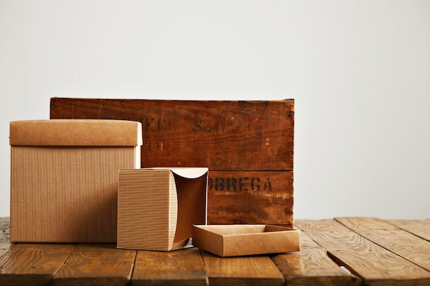 Mockup blank beige paper boxes next to a retro rough brown wooden crate isolated on white Free Photo