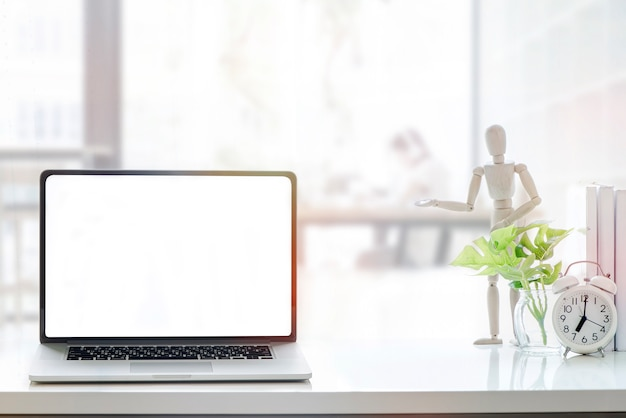 Mockup blank screen laptop on white wood table in co-working space. Premium Photo