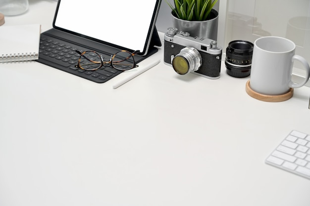 Mockup blank screen tablet, poster, books and vintage camera on workspace Premium Photo