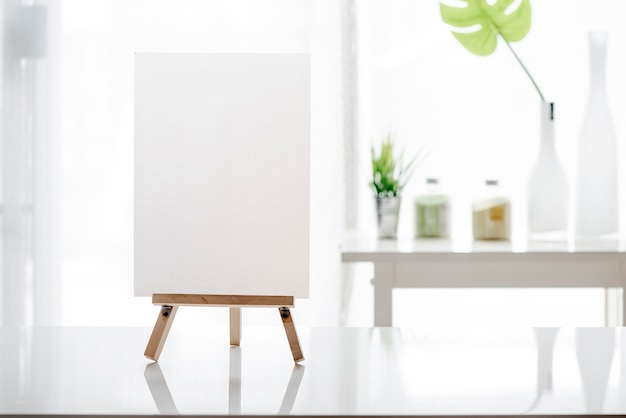 Mockup blank white menu on wooden stand on white table Premium Photo