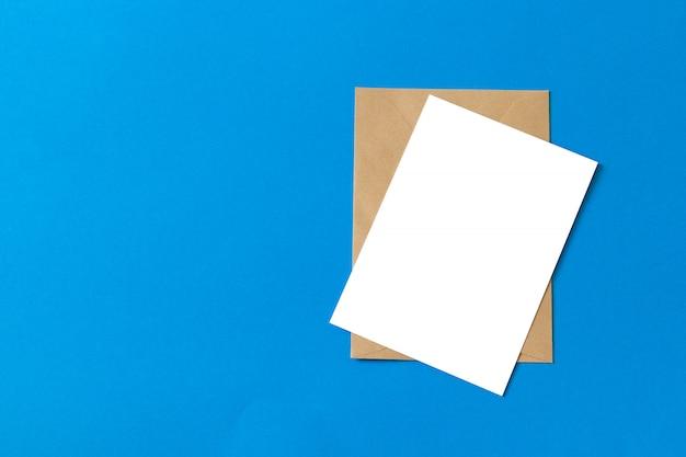 파란색 배경에 고립 된 빈 흰색 카드 이랑 갈색 크래프트 봉투 문서 프리미엄 사진