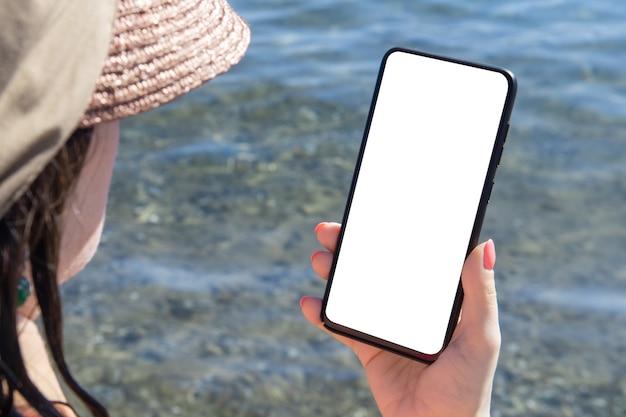 모형 핸드폰 바다 휴가. 손을 잡고 빈 흰색 휴대 전화 바다 배경을 보여주는 모형 이미지 프리미엄 사진