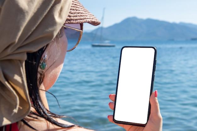 모형 핸드폰 바다 휴가. 여자 손을 바다 해변 야외에 대 한 빈 화면으로 핸드폰을 들고. 휴가 중 로밍 프리미엄 사진