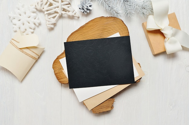 Mockup christmas black greeting card letter in envelope and gift with white tree Premium Photo