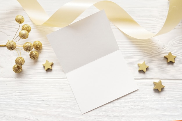 Mockup christmas greeting card top view and gold star, flatlay on a white wooden background with a ribbon Premium Photo