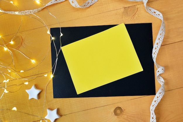 Mockup christmas yellow sheet of paper box with xmas garland on golden wooden background. Premium Photo