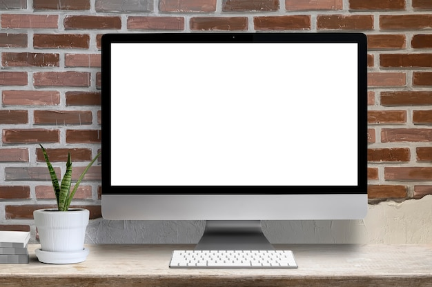 Mockup desktop computer white blank screen, houseplant and book on wooden table, blank screen for graphic design. Premium Photo